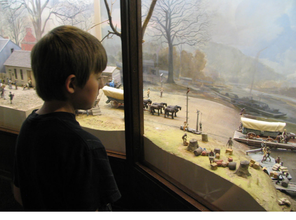 Boy looking at window display at National Road museum